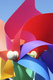 Colorful pinwheel childs toy. Close-up of childs plastic windmill toy shot against clear blue sky stock photo