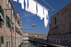 Colorful pinwheel hanging above the canal in Venice stock images