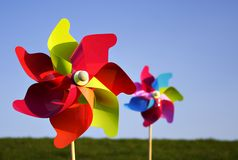 Colorful pinwheels. Two colorful pinwheels in bright sunlight on a meadow, blue sky royalty free stock images