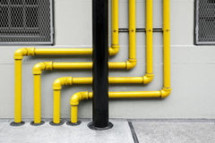 Colorful of pipes under the modern building. Technical system pipes on the exterior wall of a building stock images