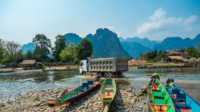 Colorful Pirogues on Nam Song River, Laos. Truck fording river behind row of brightly coloured Pirogues on the banks of the Nam Song River with impressive royalty free stock images