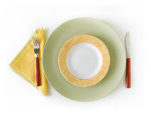 Colorful place setting. Informal place setting with empty colorful plates, fork, knife and paper napkins. View from above, isolated on white with soft shadow royalty free stock photos