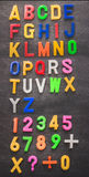 Colorful plastic alphabet on black board background Stock Photos
