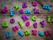 Colorful plastic alphabet letters on a wooden background Stock Image