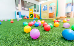 Colorful plastic ball on green turf at school playground royalty free stock photo