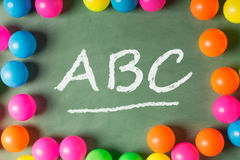 Colorful plastic balls on the green chalkboard and ABC at the ce Royalty Free Stock Photography
