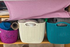 Colorful plastic baskets with natural multicolored woolen yarn. Wide knitten unfinished pink scarf hanged above. Underneath wooden Stock Image