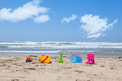 Colorful plastic beach toys lying on the beach sand Stock Photo