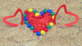 Colorful plastic beads and heart from red paper Royalty Free Stock Photo