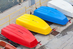 Colorful plastic boats lay on the concrete pier Royalty Free Stock Images