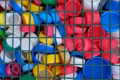 Russia, Tyumen, 09.03.2019. Colorful plastic bottle caps behind iron bars. Concept: waste Management, environmental protection, stock image