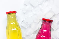 Colorful plastic bottles with ice cubes white desk background top view mockup Stock Photo