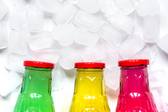 Colorful plastic bottles with ice cubes white desk background top view mockup Stock Photos