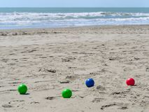 Colorful plastic bowls on the beach used to play petanque boul. Colorful plastic bowls on the beach used to play petanque or boules. rough sea in background stock image