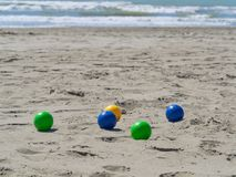 Colorful plastic bowls on the beach used to play petanque boul. Colorful plastic bowls on the beach used to play petanque or boules. rough sea in background stock photography