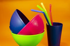 Plastic bowls cups and straws on orange background. Colorful plastic bowls cups and colored straws on orange background, a world free of plastic concept royalty free stock images