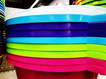 Colorful plastic bowls displayed on shelves for sale in a supermarket.  royalty free stock image
