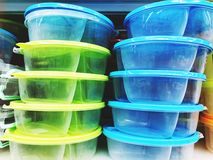 Colorful plastic bowls displayed on shelves for sale in a supermarket.  stock photo