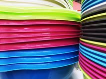 Colorful plastic bowls displayed on shelves for sale in a supermarket.  stock image