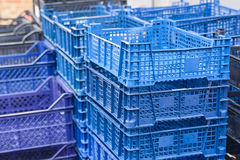 Colorful plastic boxes stacked one upon the other. Close up pile of blue and violet plastic boxes outside Stock Photo