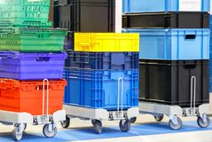 Colorful plastic boxes stacked one upon the other on warehouse trolley or platform trolley.  stock image