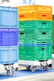 Colorful plastic boxes stacked one upon the other on warehouse trolley or platform trolley.  royalty free stock photos
