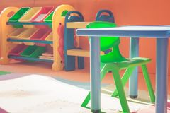Colorful plastic chair and desk for children playing and learning in kids room in vintage style. stock photos