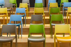 Colorful plastic chairs on wooden steps floor Stock Photography