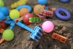 Colorful plastic children toys in sand pit Royalty Free Stock Image