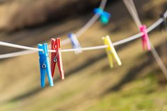 Colorful plastic clothes pegs on white clothesline, fashion business concept Royalty Free Stock Images