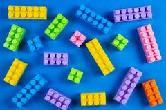 Colorful plastic construction blocks pattern on blue background.  stock photography