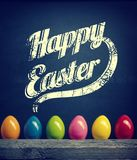 Colorful plastic Easter eggs, Happy Easter. Colorful plastic Easter eggs in row on a black chalkboard with Happy Easter, vintage stylized Royalty Free Stock Photos