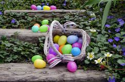 Stairs Full of Eggs. Colorful plastic eggs spilled all over wooden stairs outside. Rattan basket on it`s side full of plastic eggs. All surrounded by white and Royalty Free Stock Images