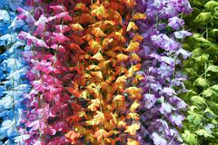 Colorful plastic flower garlands hanging down stock photos
