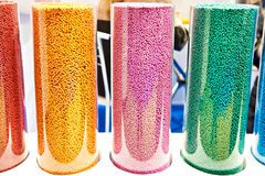 Colorful plastic granular polymer. In glass flasks Royalty Free Stock Photos