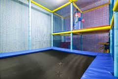 Colorful plastic jungle for kids with a trampoline. Modern children`s playground indoor. Colorful plastic jungle for kids with a trampoline. Gym child playroom royalty free stock photos