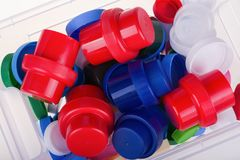 Colorful plastic lids in a box on white background Stock Photos