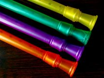 Colorful plastic musical instruments. In orange, purple, green, and yellow on a deep brown background Stock Photography