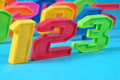 Colorful plastic numbers 123 on a blue background Royalty Free Stock Photo