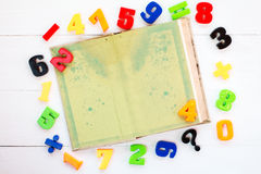 Colorful plastic numbers and open book Royalty Free Stock Photos