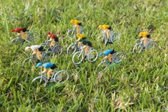 Colorful plastic road cyclists outdoor in the grass. Yellow jersey leader. Competition. Peloton. Plastic road cyclists. Competition concept. Teamwork and royalty free stock photos