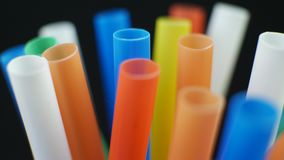 Colorful plastic rod of straw. Rotates on black color background stock footage