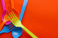 Colorful plastic spoon. On orange background Royalty Free Stock Photos