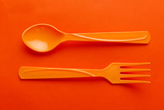 Colorful plastic spoon. On orange background Stock Image