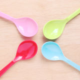Colorful plastic spoons on wood Royalty Free Stock Images