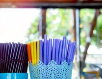 Colorful plastic straws in plastic container in coffee shop. Colorful plastic straws, Purple, yellow, orange and brown in blue plastic container in coffee shop stock photo