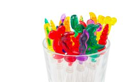 Colorful plastic swizzle sticks in glass on white background wit. H Clipping Path Stock Photography