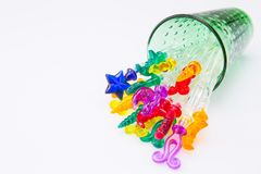 Colorful plastic swizzle sticks spilled from glass on white back. Ground Royalty Free Stock Photos