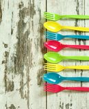 Colorful plastic tableware on wooden Stock Image
