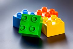 Colorful plastic toy building blocks on gray background. Four colorful plastic toy building blocks on gray background stock images